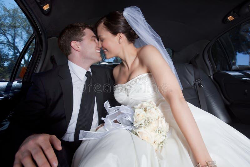 Couples de nouveaux mariés dans la limousine image libre de droits