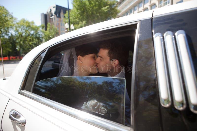 Couples de nouveaux mariés embrassant dans la limousine photos libres de droits