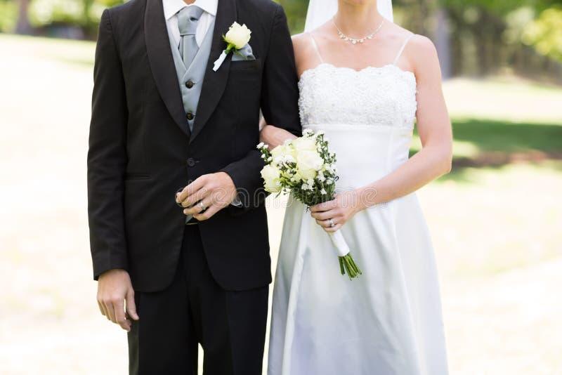 Couples de nouveaux mariés tenant des mains en parc photos libres de droits