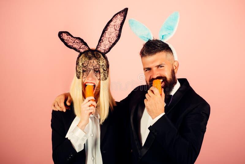 Couples de Pâques prêts à jaillir vacances Le lapin drôle de Pâques grignote une carotte comme un lièvre Joyeuses vacances et Pâq image stock