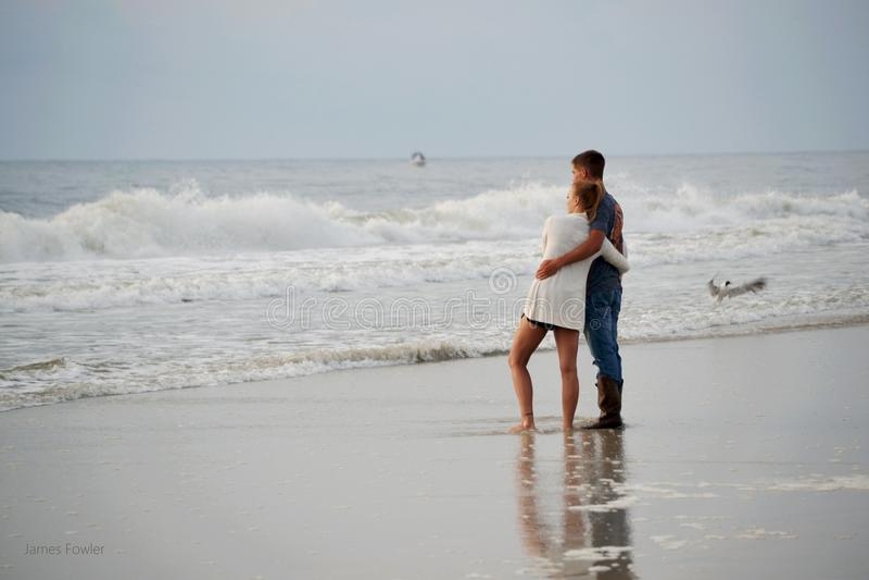 couples de plage étreignant des jeunes images libres de droits