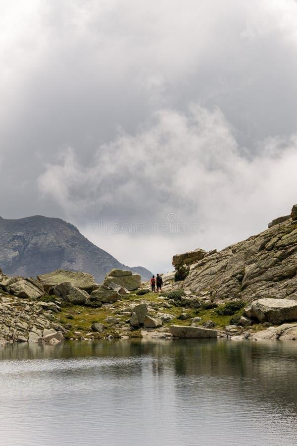 Couples de promenade de randonneurs près du lac photographie stock libre de droits