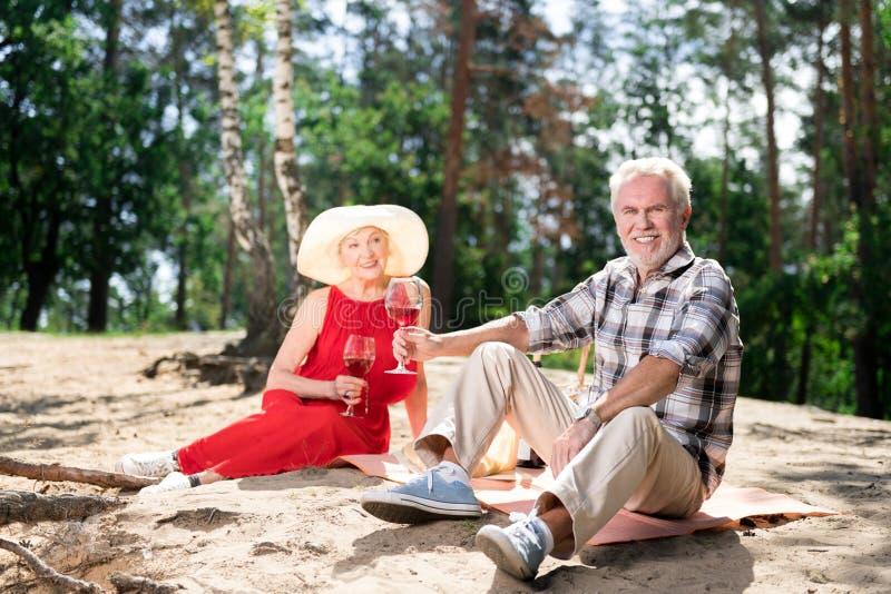 Couples de rayonner l'épouse pluse âgé et le mari s'asseyant sur le sable ayant le pique-nique photographie stock libre de droits