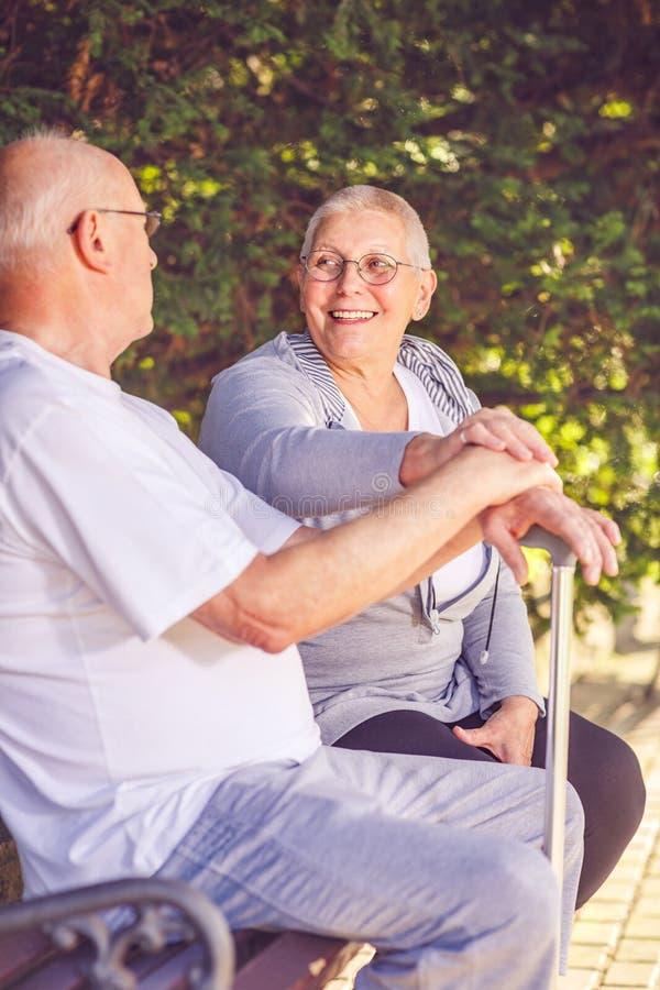 Couples de retraité se reposant sur un banc de parc image libre de droits