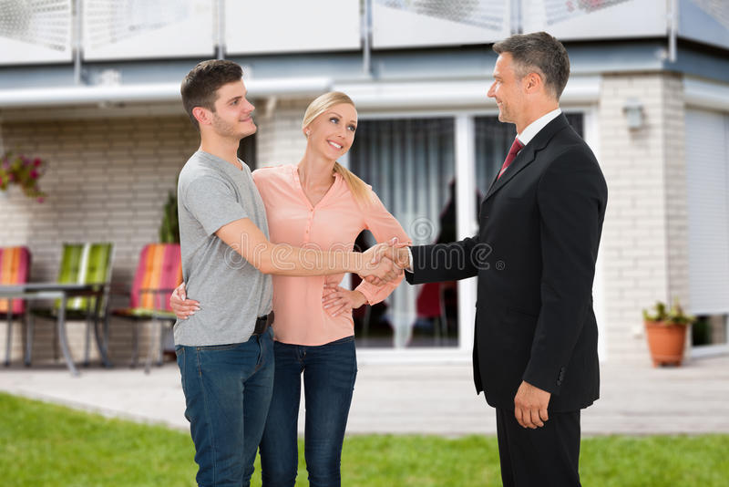 Couples de Shaking Hands With d'agent immobilier images stock
