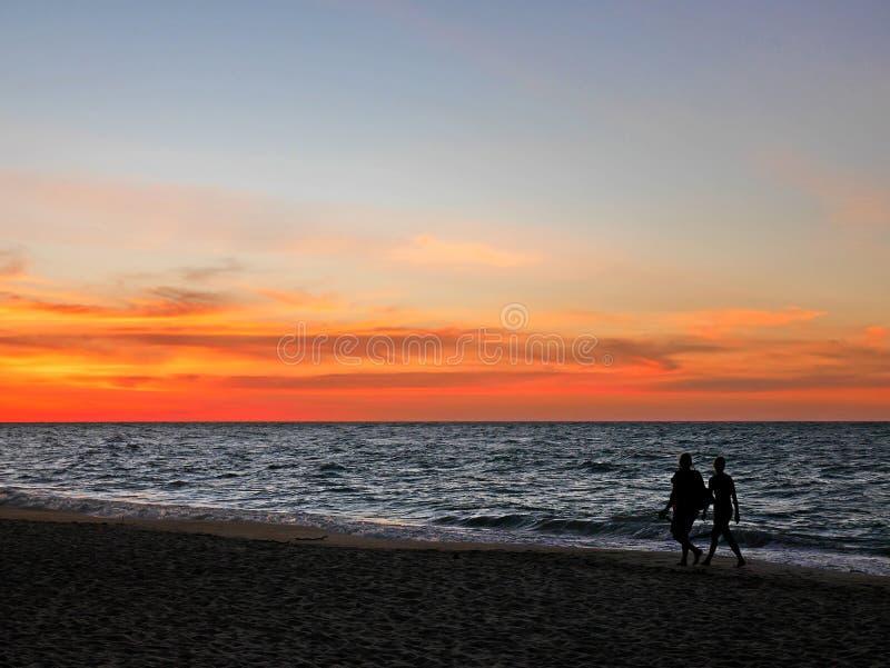 Couples de silhouette marchant le long de la plage de coucher du soleil images libres de droits