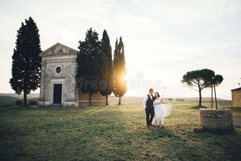 Couples de sourire élégants heureux marchant et embrassant en Toscane, AIE image libre de droits