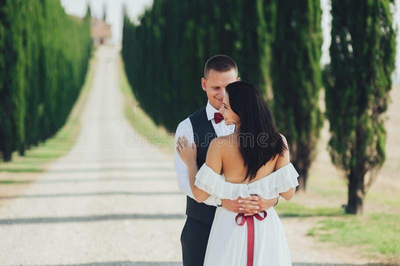 Couples de sourire élégants heureux marchant et embrassant en Toscane, AIE photo stock
