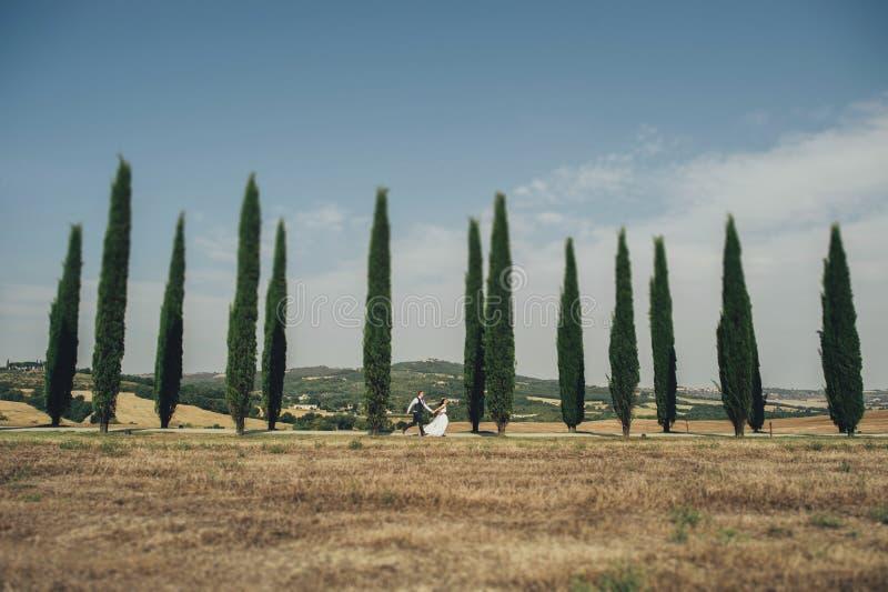Couples de sourire élégants heureux marchant et embrassant en Toscane, AIE images stock