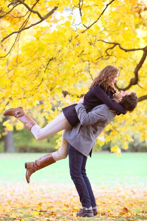Couples de sourire étreignant en parc d'automne photo stock