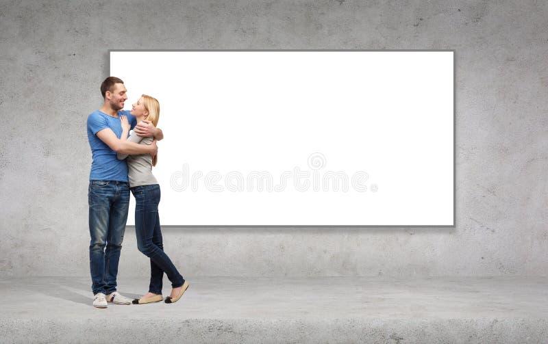 Couples de sourire étreignant et regardant l'un l'autre image libre de droits