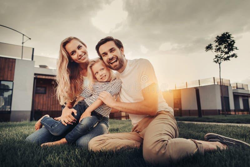 Couples de sourire étreignant l'enfant gai pendant le coucher du soleil photo stock