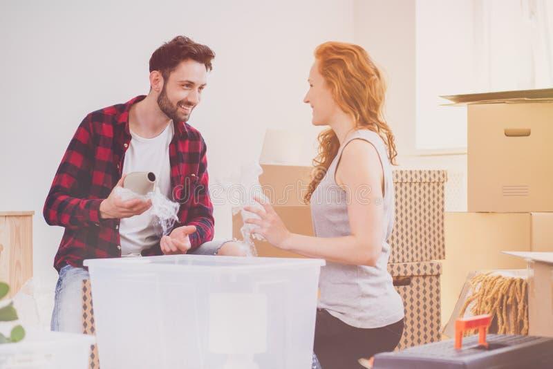 Couples de sourire appréciant emballant la substance tandis que déplacer-dans la nouvelle maison photo stock