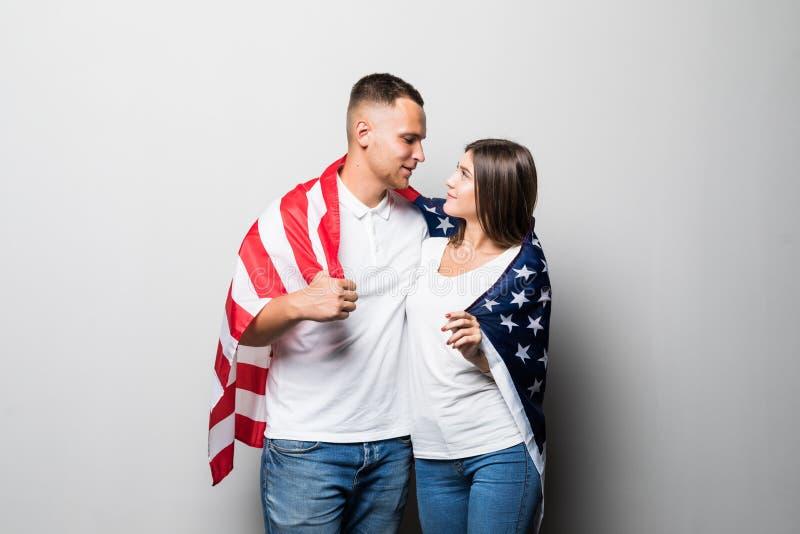 Couples de sourire dans l'amour posant avec le drapeau des Etats-Unis d'isolement sur le fond gris Gar?on beau heureux dans la ch photos libres de droits