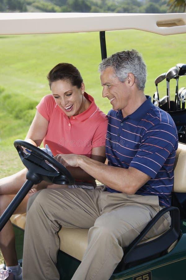 Couples de sourire dans le chariot de golf photos libres de droits