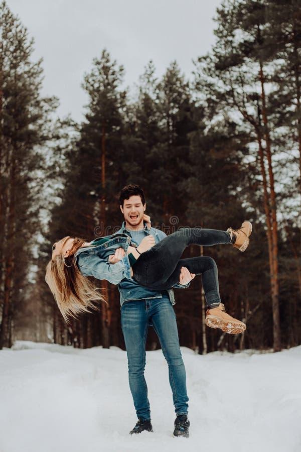 Couples de sourire gais heureux des jeunes dans des costumes de denim dans la forêt neigeuse en hiver Place pour le texte Vacance photo libre de droits