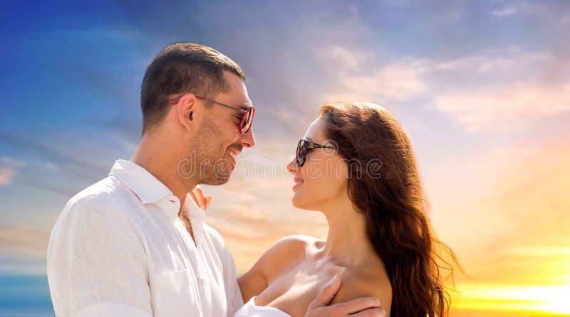 Couples de sourire heureux dans étreindre de lunettes de soleil image libre de droits