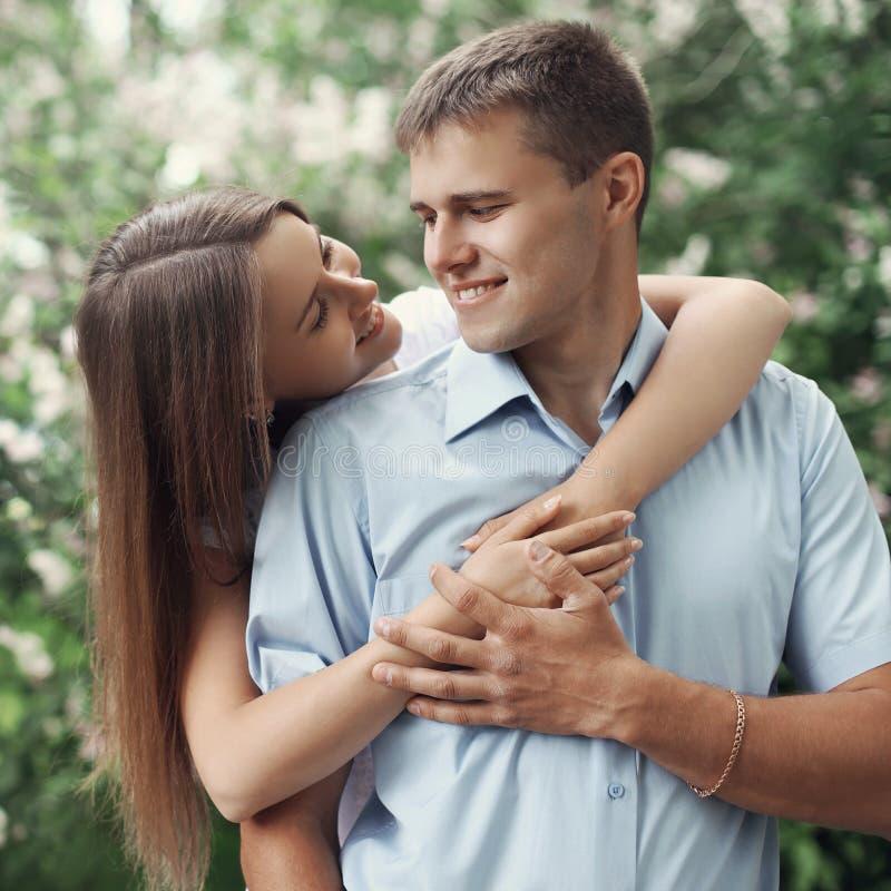 Couples de sourire heureux de portrait les jeunes dans l'amour au-dessus d'un ressort fleurissant font du jardinage image stock
