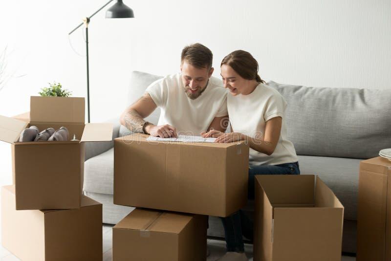 Couples de sourire heureux discutant le plan architectural de maison photographie stock libre de droits