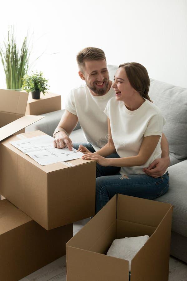 Couples de sourire heureux discutant le plan architectural de maison images stock