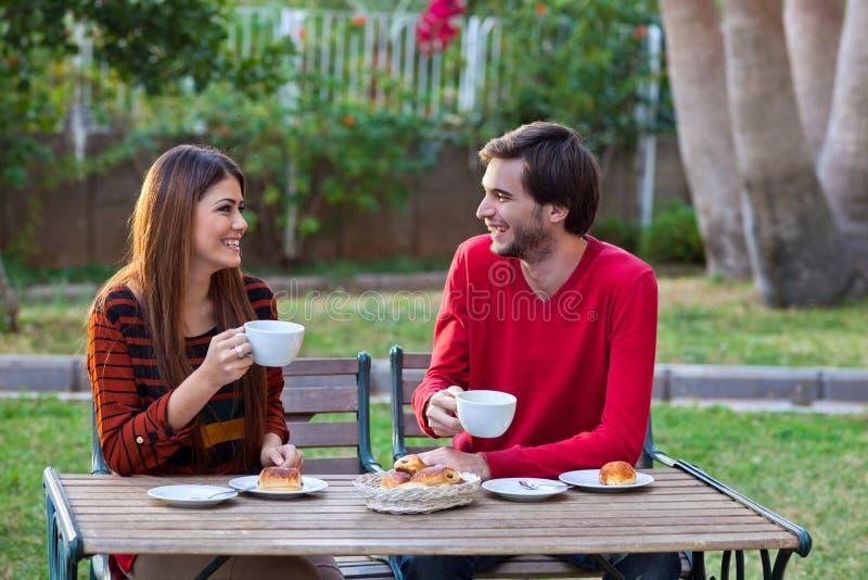 Couples de sourire heureux prenant le déjeuner photographie stock libre de droits