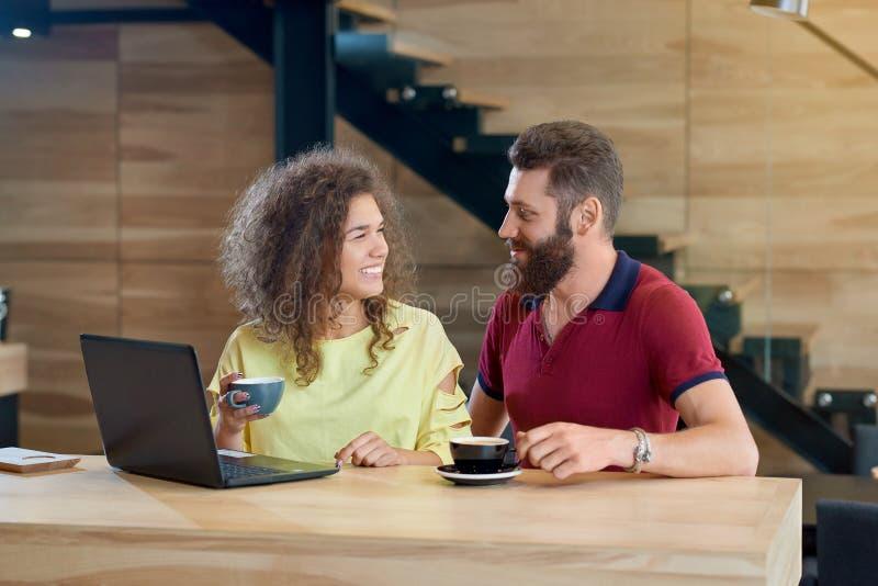 Couples de sourire heureux regardant sur l'un l'autre le café potable en café image libre de droits