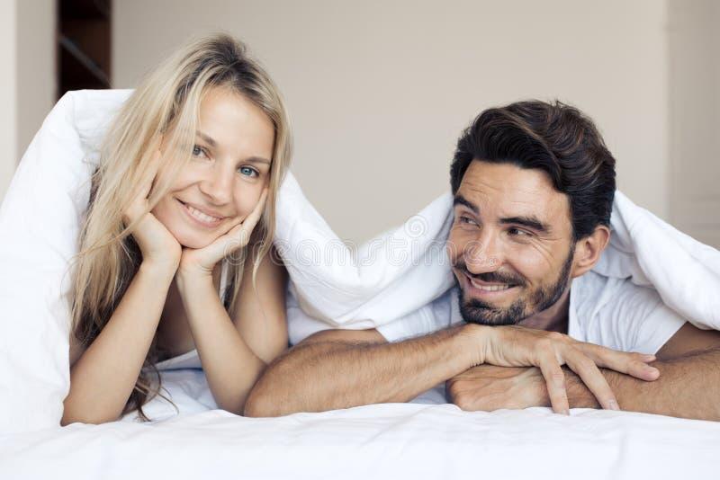 Couples de sourire heureux se trouvant sur le lit dans la chambre à coucher image stock