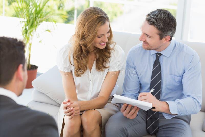 Couples de sourire lors de la réunion avec un conseiller financier images stock