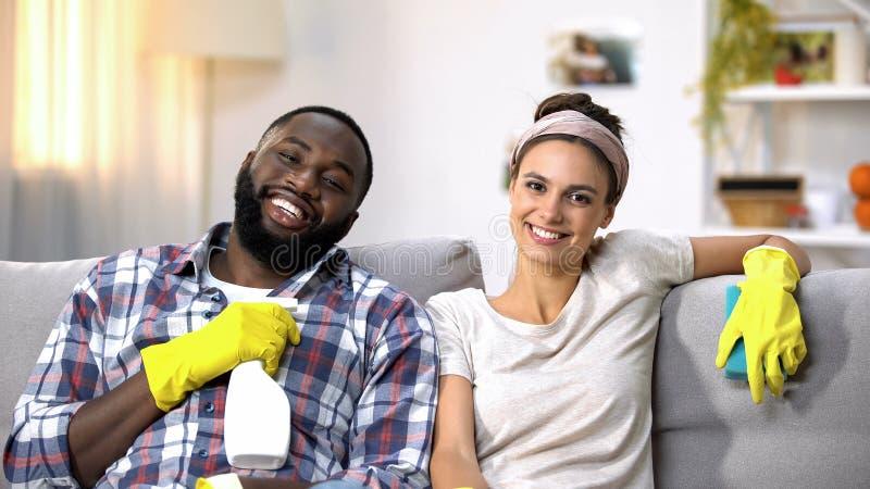 Couples de sourire de métis tenant le jet de détergent, heureux sur les travaux domestiques faits photo libre de droits