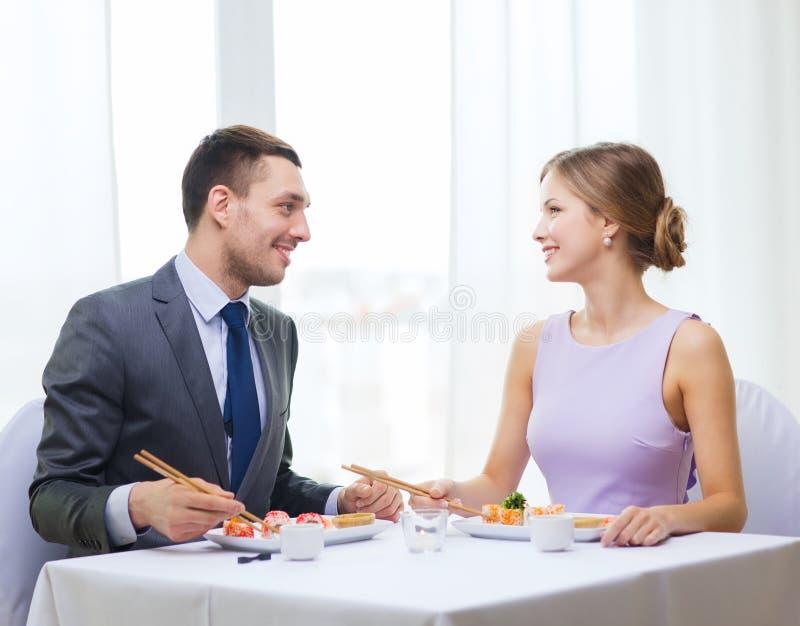 Couples de sourire mangeant des sushi au restaurant images libres de droits