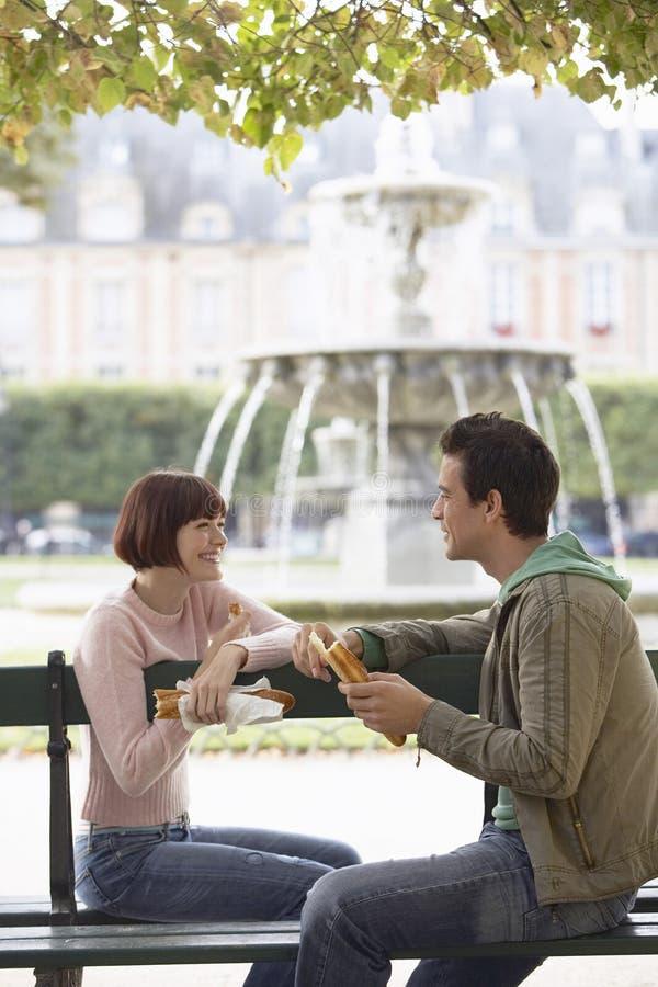 Couples de sourire mangeant la baguette sur le banc de parc photographie stock libre de droits