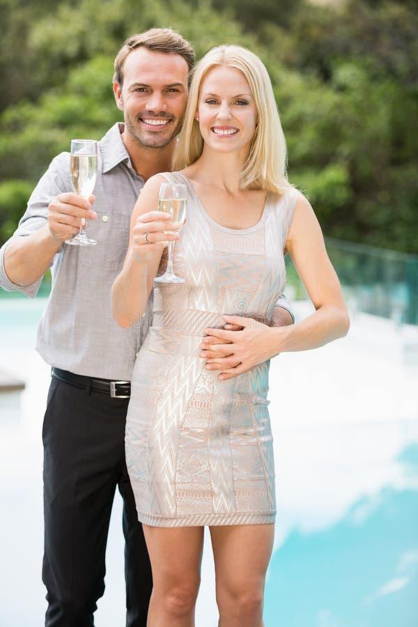 Couples de sourire montrant des cannelures de champagne image stock