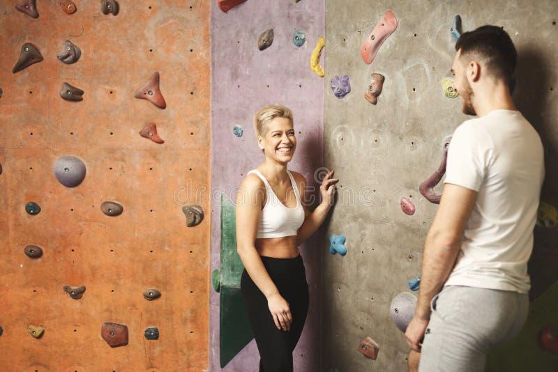 Couples de sourire parlant près du mur s'élevant artificiel photographie stock