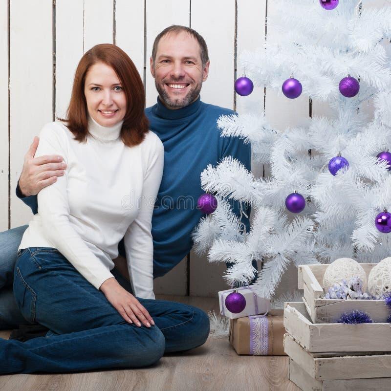 Couples de sourire près d'un arbre de Noël image stock
