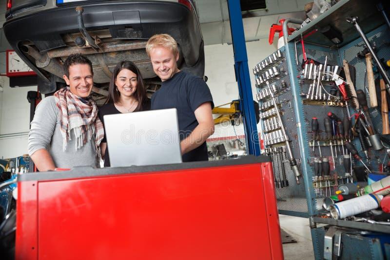 Couples de sourire restant avec le mécanicien à l'aide de l'ordinateur portatif photos stock