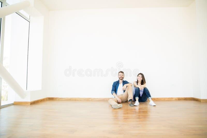 Couples de sourire se reposant dans la chambre vide du nouvel appartement photos libres de droits