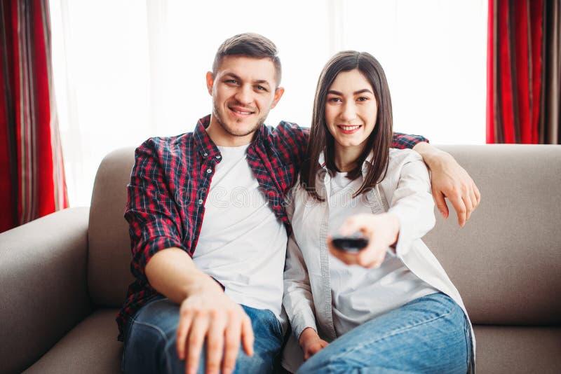 Couples de sourire se reposant sur le divan et la montre TV photo libre de droits