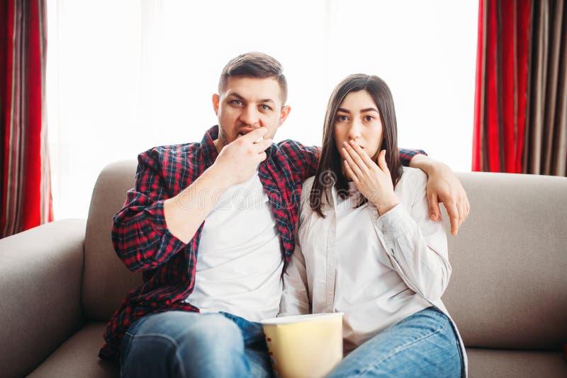 Couples de sourire se reposant sur le divan et la montre TV images libres de droits