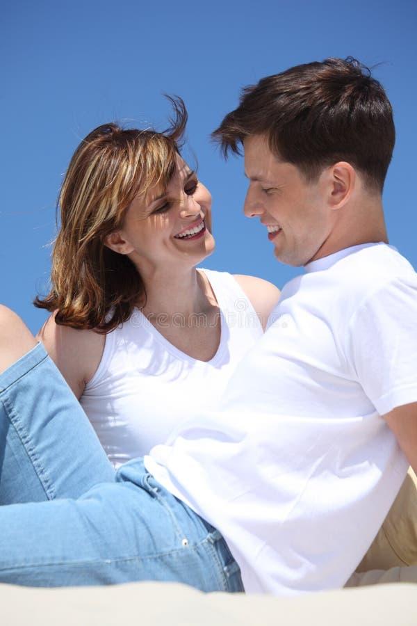 Couples de sourire se reposant sur le sable photo stock