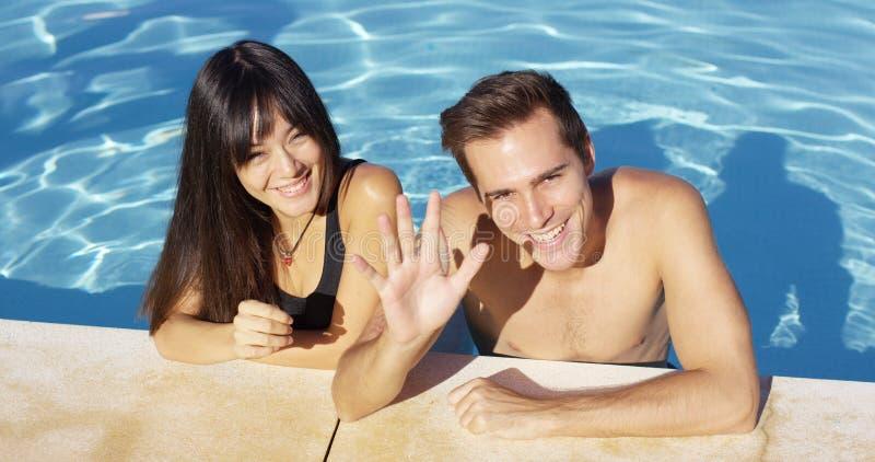 Couples de sourire se tenant dans la vague claire de piscine photo stock