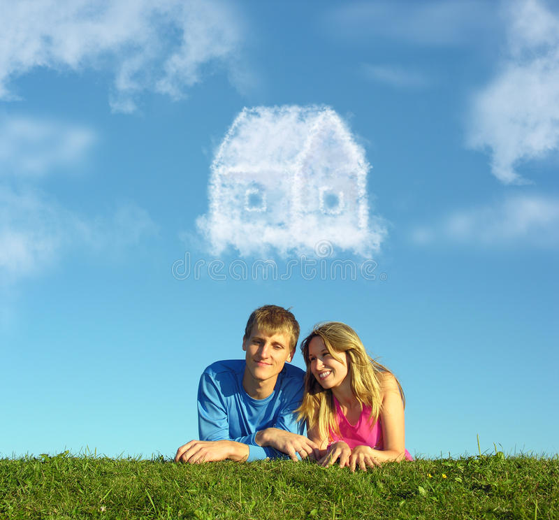 Couples de sourire sur la maison de nuage d'herbe et de rêve photos libres de droits
