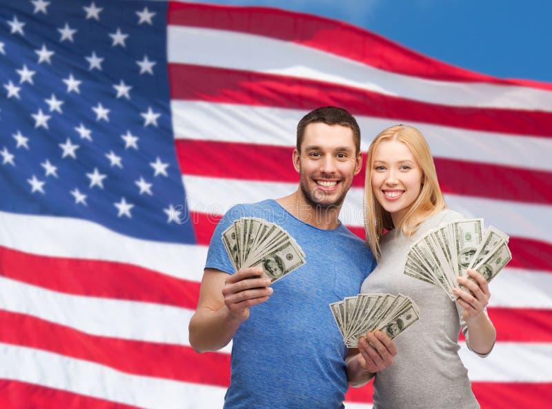 Couples de sourire tenant l'argent d'argent liquide du dollar photographie stock libre de droits