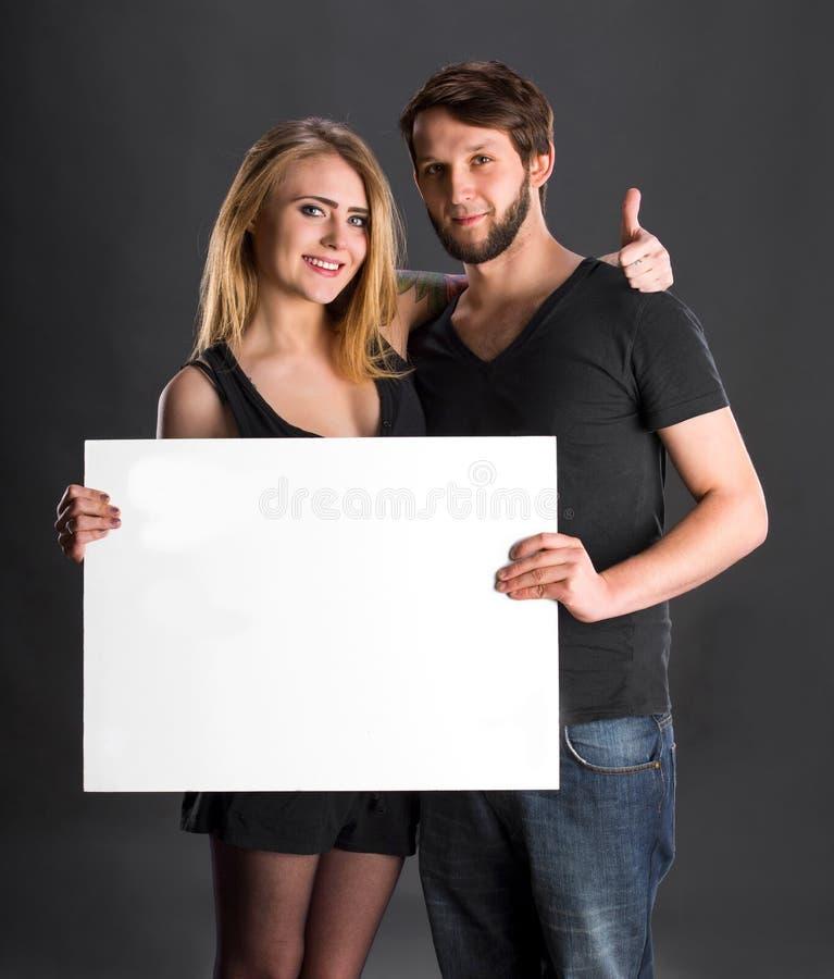 Couples de sourire tenant le grand conseil blanc vide photos libres de droits