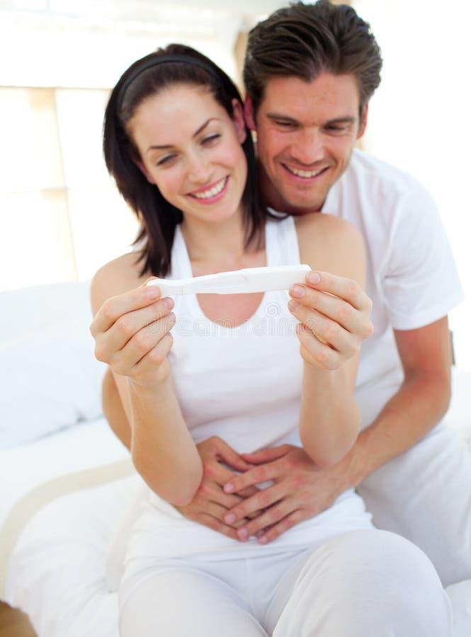 Couples de sourire trouvant des résultats d'essai de grossesse photo stock