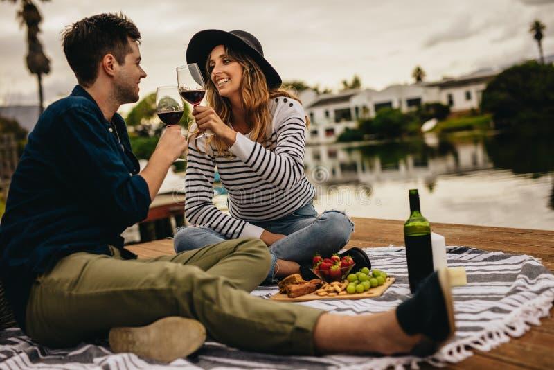 Couples de sourire une date près d'un lac images libres de droits