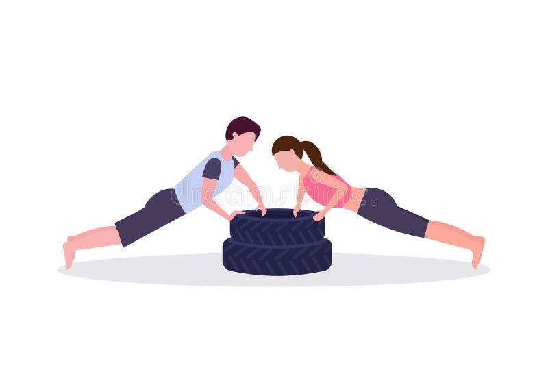 Couples de sports faisant l'exercice de pompe sur la femme d'homme de pneus établissant dans le crossfit de gymnase formant le co illustration libre de droits