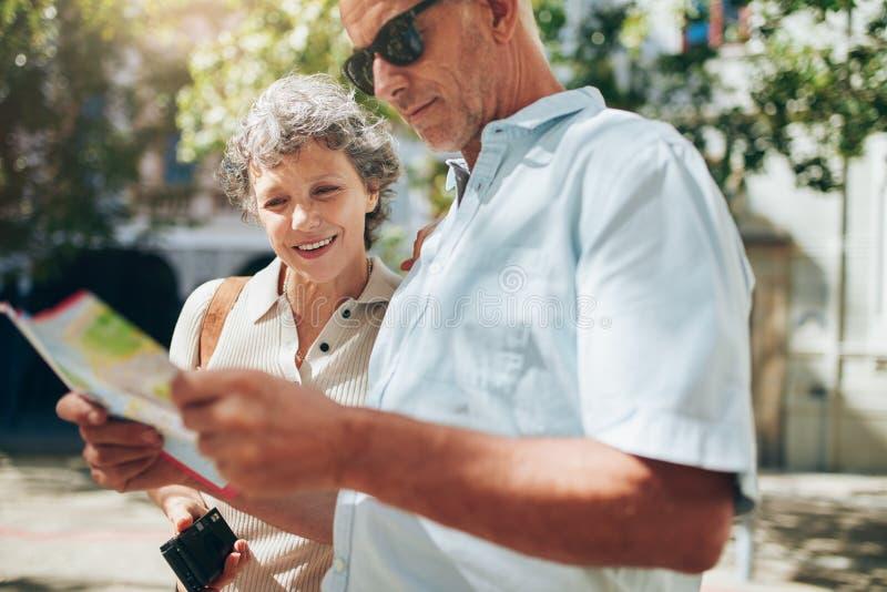 Couples de touriste lisant la carte de ville photos stock
