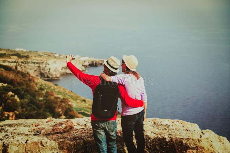 Couples de touristes augmentant en montagnes prenant le sefie, concept de voyage images libres de droits