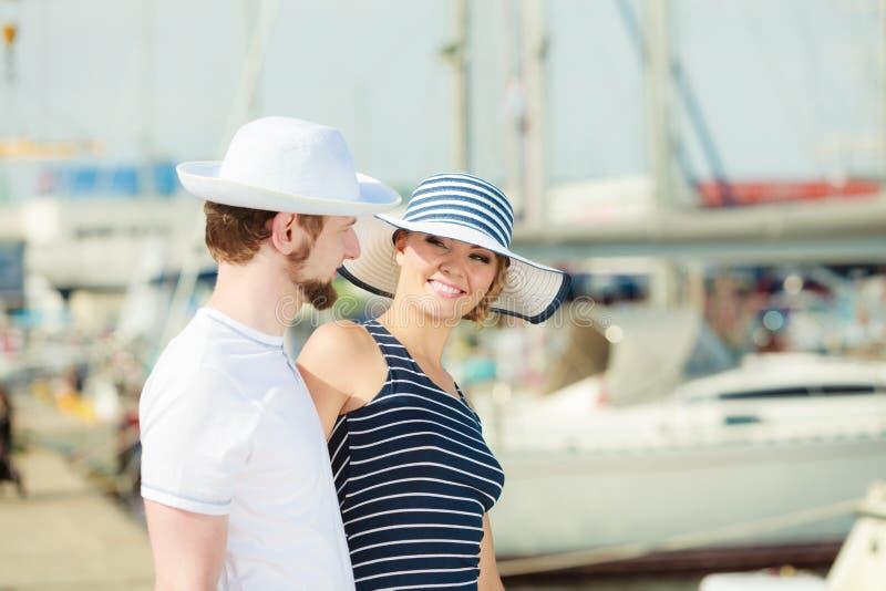 Couples de touristes dans la marina contre des yachts dans le port photos libres de droits