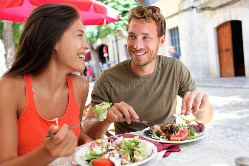 Couples de touristes de restaurant mangeant au café extérieur image libre de droits